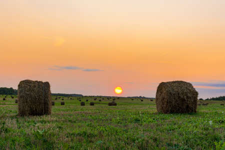 Two bales of straw on foreground on the autumn meadow during wonderful sunset light. Nature background