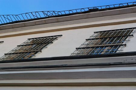 Fragment of building including cornice and window with grating photo