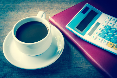 Cup of coffee, books and calculator, on table wood photo
