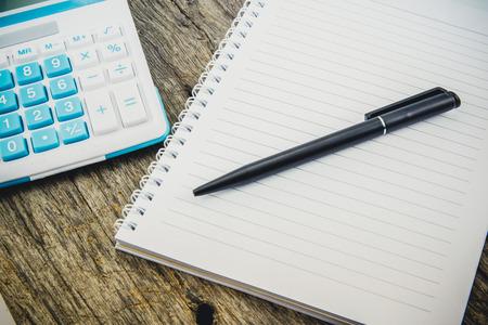 carta e penna: nota carta, penna e calcolatrice sul tavolo in legno