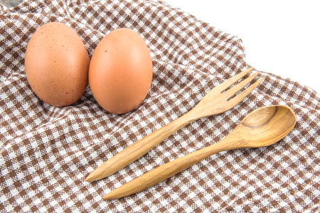 fresh eggs and spoon wooden on table