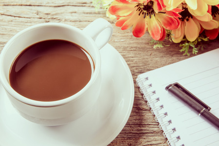Cup of coffee, pen and notepad on wooden table