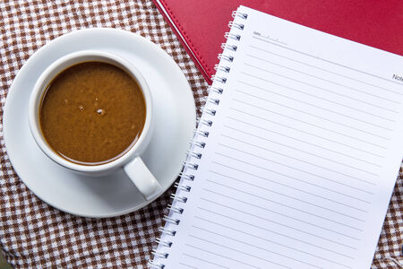 Cup of coffee and notepad on wooden table photo