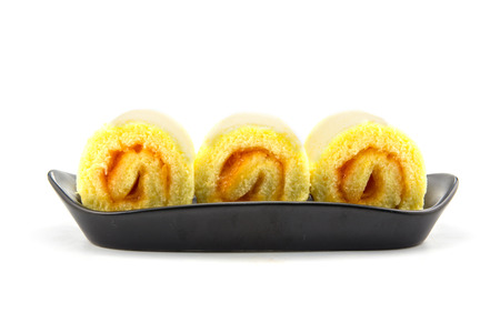 oreochromis: Orange roll cake on plate white background Stock Photo