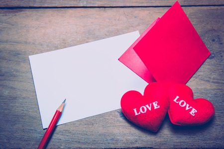 red envelop with shape heart pillow on text love, sheet of paper and on wooden background photo