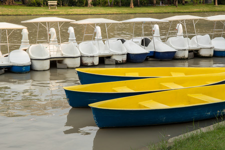 rowboats: Row of Swan Boats Style and Two Rowboats Floating