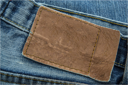 jeans: Blank leather jeans label sewed on a blue jeans. Stock Photo