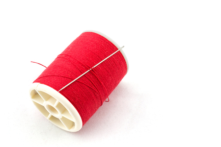 hilo rojo: Spool of red thread and needle on white background