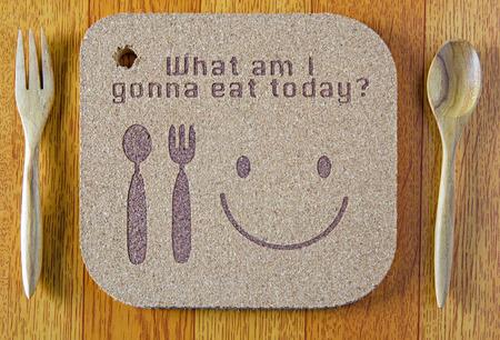"""houtstructuur schrijven """"wat ga ik vandaag eten"""" concept en lepel op houten achtergrond"""