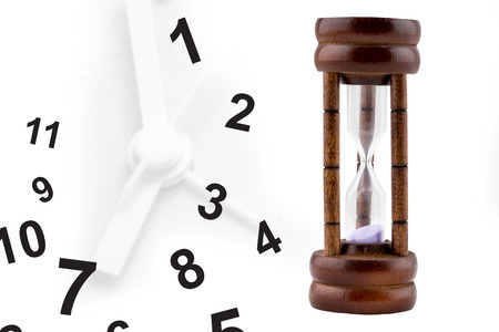 concurrent: Time running out: sand falling inside hourglass, with analog clock in background, Time gradually running out Stock Photo