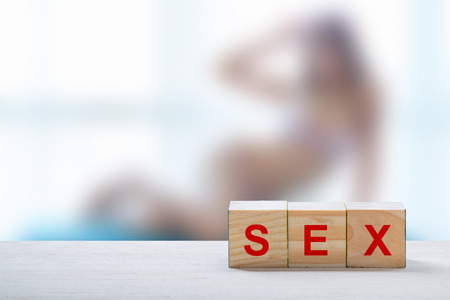 sex education: text blocks spell sex and girl nude blur background. Stock Photo