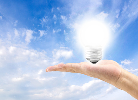electricity background: Energy efficient bulb in hand with blue sky in background, save energy concept