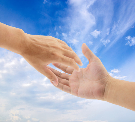 hands solution: helping hands on sky background Stock Photo