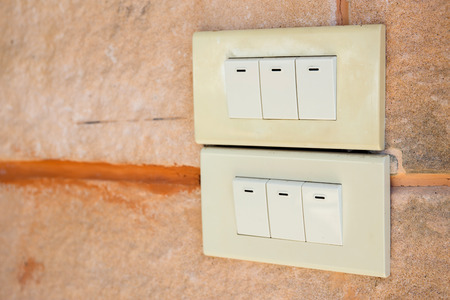 dimmer: White light switch on  yellow cement wall