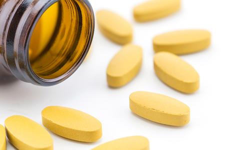 Pillen van vitamine C gemorst open container op witte achtergrond. Stockfoto
