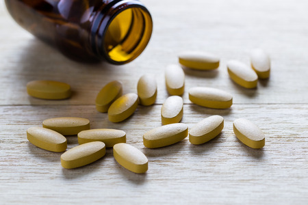 Pills of vitamin C spilled out open container on wood background.