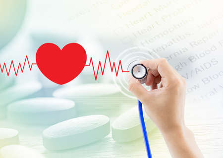 Medical, hand holding stethoscope, heart beat graph and pill, document abstract background Stock Photo