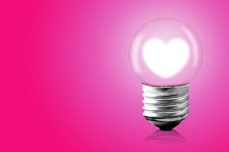 electric bulb: Heart glow inner electric lamp on pink background. Stock Photo