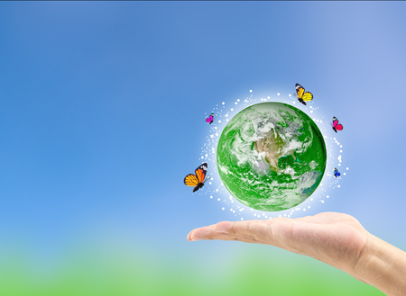 Earth planet with butterfly in hand against green blurred background. Earth day. Spring holiday concept. Elements of this image furnished by NASA 스톡 콘텐츠