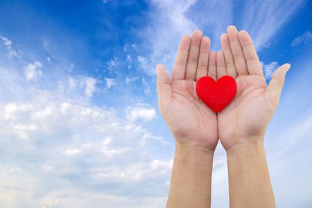 Hart in de hand op hemelachtergrond