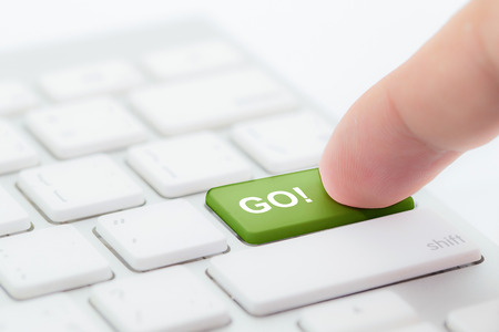 Hand pushing go green button on keyboard