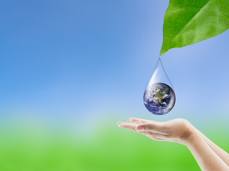 Earth in water drop reflection under green leaf hold hand