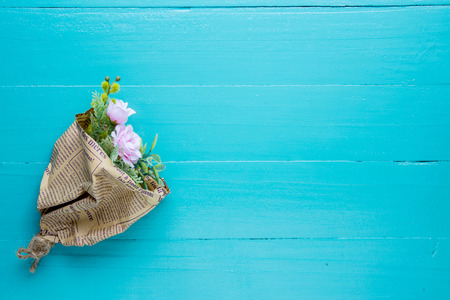 fake newspaper: Bouquet of beautiful fresh flower artificial wrapped in paper, newspaper on wood background Stock Photo