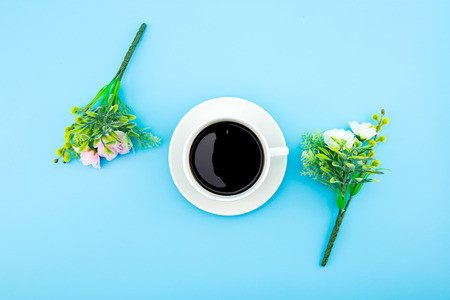 Cup of coffee surrounded by artificial flowers. Creative flowers. Flat lay, top view on blue background