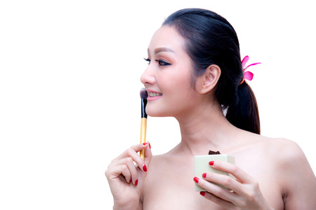 Closeup portrait of a asian woman applying dry cosmetic tonal foundation on the face using makeup brush, on pink background.