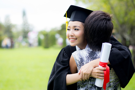 young female graduate hugging her friend at graduation ceremony Archivio Fotografico