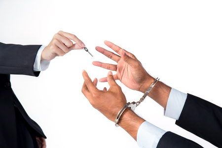 handcuffs: businessman in handcuffs and woman hand offering key solving business ideas concept isolated on white background