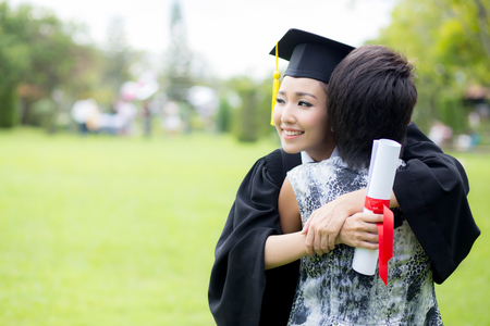 young female graduate hugging her friend at graduation ceremony 写真素材