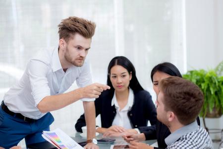 Groep zakenlieden kijken naar zakenman blameert zijn collega in de vergadering Stockfoto