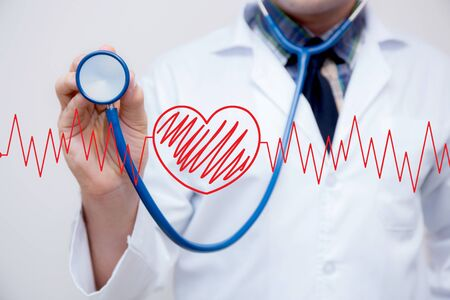 graph red heart with the heart is a part of a cardiogram with stethoscope holding hand - Concept of medical examination.