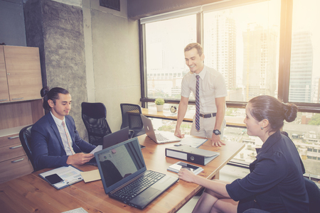 Businesspeople with leader discussing together in conference room during meeting at office.