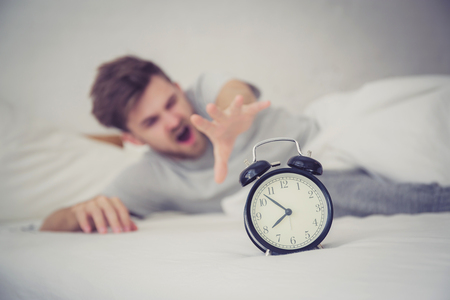 man sleepy nationality american reaching for the alarm clock sleeping on bedroom. Banco de Imagens