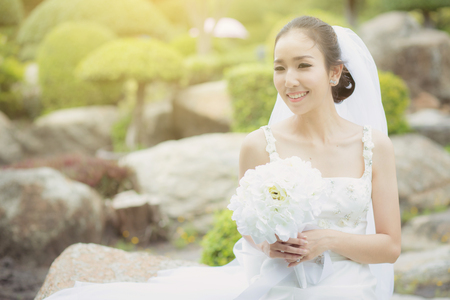beautiful young woman on wedding day in white dress in the garden. Female portrait in the park - Selective focus.