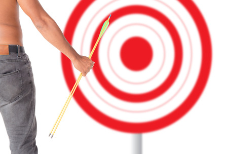 Asian man holding bow and shooting to archery target. Rear view, businessman aiming at target with bow and arrow, target success concept.
