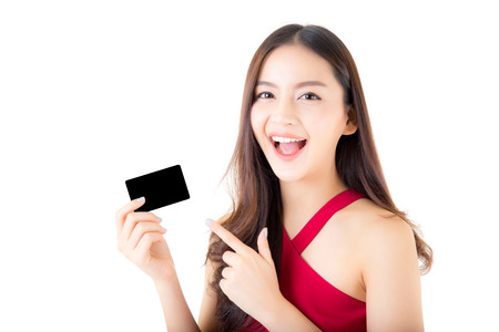 Asian young woman with red dress holding a credit card thinking to spend money lots isolated on white background. Banco de Imagens