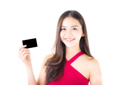 Aziatische jonge vrouw met rode kleding die een creditcard houden die die geldkavels denken te besteden op witte achtergrond worden geïsoleerd. Stockfoto