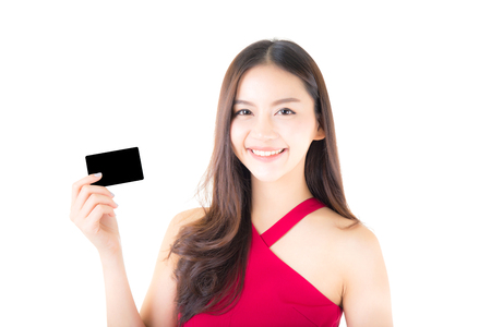 Asian young woman with red dress holding a credit card thinking to spend money lots isolated on white background. Archivio Fotografico