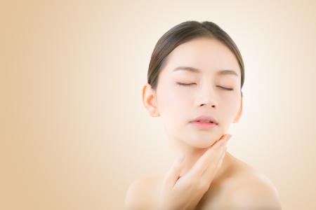 Bella ragazza con il concetto di cura di trucco, della donna e di pelle / ragazza attraente dell'Asia che smilling sul fronte su fondo giallo. Archivio Fotografico - 84576751