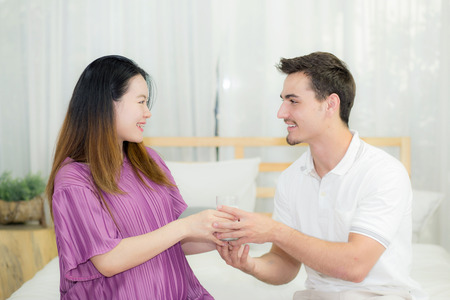 lovely pregnant woman: Asian handsome husband takes care about pregnant woman with gives a glass of milk lovely pregnant. Stock Photo