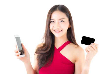 Vrolijke Aziatische jonge vrouw met telefoon en creditcard op witte achtergrond, winkelend online concept. Stockfoto