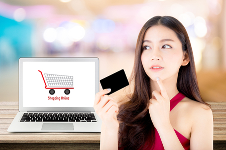 Beautiful woman asia using credit card shopping online with labtop, notebook on table top and bokeh background, girl thinking payment with computer.