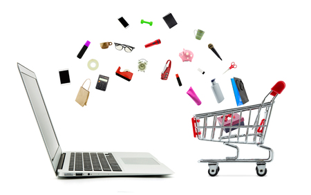 Shopping cart and laptop computer with products isolated on white background, shop online concept. Stock Photo