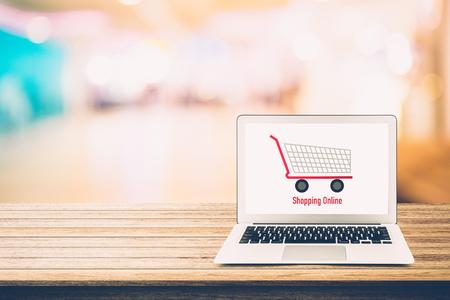 Online einkaufen mit Labtop, Notebook auf Tischplatte und Bokeh-Hintergrund, Shop mit Computer. Standard-Bild - 87556366