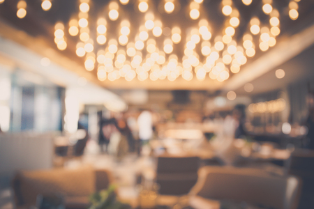 Blur abstract bokeh light background with restaurant or coffee shop or pub modern luxury style with people celebrate and dinning warm tone. For create montage product display.
