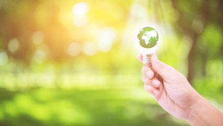 Hand holding a light bulb with energy green world inside on nature background, environment and ecology concept - Elements of this image furnished by NASA. Stock Photo