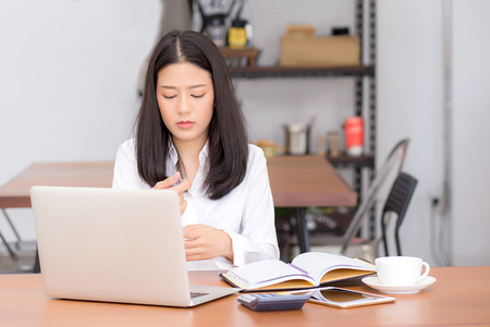 Beautiful asian young woman working on laptop sitting at coffee shop